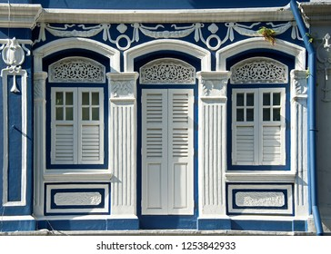 Front view of traditional vintage Singapore Peranakan or Straits Chinese shop house or shophouse exterior with antique white wooden shutters and ornate columns in the historic downtown area
