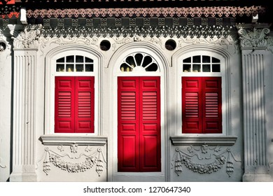 Front view of traditional vintage Singapore Straits Chinese or Peranakan shop house with antique red wooden louvered shutters, arched windows and ornate carvings in  historic Chinatown