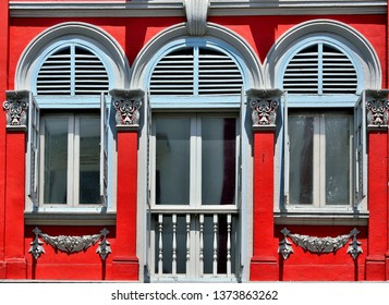 Front view of traditional vintage Singapore Straits Chinese or Peranakan shop house with antique white wooden louvered shutters, arched windows and red exterior in historic Little India Singapore