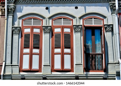 Front view of traditional vintage Singapore shop house or shophouse with arched windows and antique red and white wooden shutters in historic Tanjong Pagar