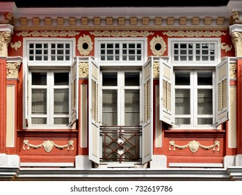 Front view of traditional vintage Singapore Peranakan or Straits Chinese shop house with ornate colourful exterior and antique white louvered shutters in historic Chinatown