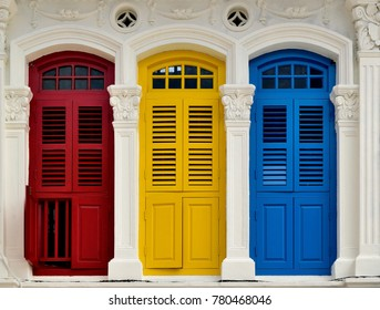Front view of traditional vintage Singapore shop house or shophouse with antique red, blue and yellow wooden shutters in historic Little India