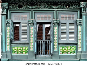 Front view of traditional vintage Straits Chinese or Peranakan Singapore shop house or shophouse with antique wooden shutters and green tiles in historic Joo Chiat