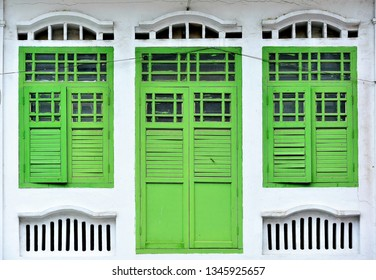 Front view of traditional vintage Straits Chinese or Peranakan Singapore shop house with antique green wooden shutters and white exterior in historic Little India