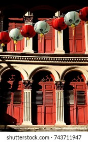 Front view of traditional vintage Straits Chinese or Peranakan Singapore shop house or shophouse with antique red shutters and a string of Chinese lanterns celebrating Chinese New Year in Chinatown.