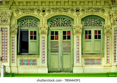 Front view of traditional vintage Straits Chinese or Peranakan Singapore shop house or shophouse with antique green wooden shutters and green exterior in historic Little India