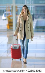 Front view of a traveler woman walking carrying a suitcase in an airport corridor