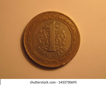 Front view of Turkish coin. 1 Turk Lirasi from Turkey. Great for numismatic collection. Shiny coin isolated on yellow surface of paper.