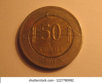 Front view of Turkish coin. 50 kurus from Turkey. Great for numismatic collection. Shiny coin isolated on yellow surface of paper.