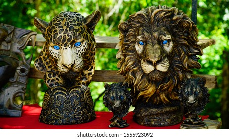 Front view of Two beautiful heads carved in wood and painted by hand, one of lion and another of jaguar. They are usually used as decorative objects
