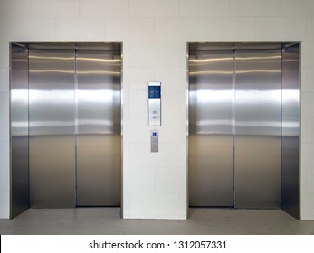 Front view of two closed stainless steel elevator doors in hospital lobby.