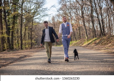 front view, two gay man walking in forest, on asphalt road. Together holding hands. Their puppy dog walking with them too close by.