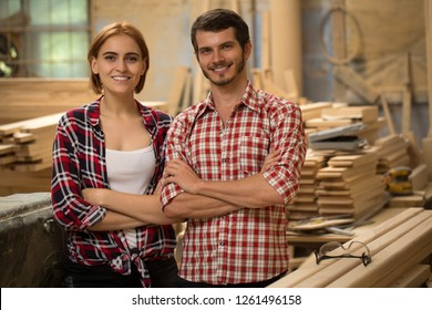 Front view of two handsome and positive carpenters standing, looking at camera and posing. Young and talented woodworkers smiling, wearing in checked shirts. Background of joiner's shop.