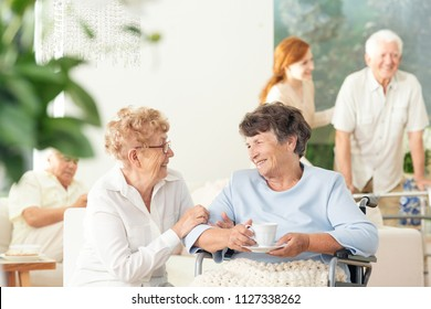 Front view of two happy geriatric women talking and holding hands in a private luxury day care center. Other seniors in the blurred background.