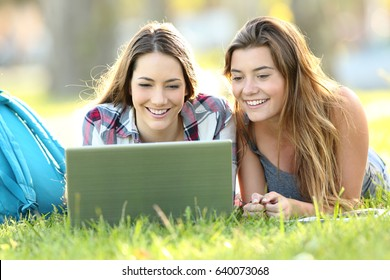Front view of two happy students watching on line content with laptop lying on the grass in a park