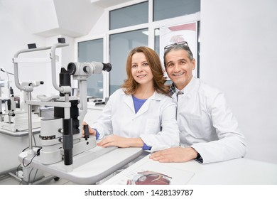 Front view of two oculists working with slit lamp together in optical store. Two eyes doctors sitting at table, looking at camera, smiling and posing in clinic. Concept of ophthalmology and health.