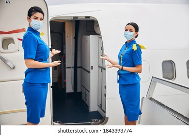 Front view of two slim female flight attendants standing at the entrance to the airplane