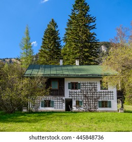 Front view to typical traditional austrian house - a wooden roof, black door, windows with two shutters, decorative grid with twine plants - blue sky, mountains peak and green forest in the background