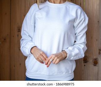 The front view of unrecognizable woman wear white blouse, behind her is wooden board. Empty space on blouse for design or inscription. Fashion mockup with copy space.