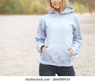 The front view of unrecognizable woman wearing light grey hoodie. She stands on the beach. Copy space on empty area on her blouse for design or inscription. Fashion mockup. Sweatshirt template.