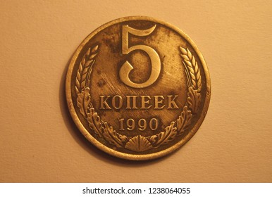 Front view of USSR coin. Kopecks from Soviet Union. Great for numismatic collection. Shiny coin isolated on yellow surface of paper. Historical old retro coin of kopek (cent).