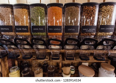 Front view of variety of dry food displayed in grocery store. Zero waste shopping - shelf with glass jars full of pea and lentil seeds in organic shop.
