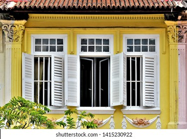 Front view of vintage Peranakan or Straits Chinese shop house exterior with yellow facade, antique white wooden louvered shutters in historic Everton Park Singapore