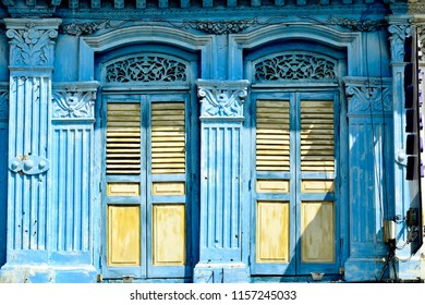 Front view of vintage Singapore Peranakan or Straits Chinese shop house exterior with bluefacade, antique yellow wooden louvered shutters and arched windows in historic Geylang