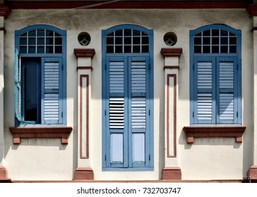 Front view of vintage traditional Peranakan or Straits Chinese Singapore shop house with ornate exterior, antique blue louvered shutters and arched windows in historic East Coast