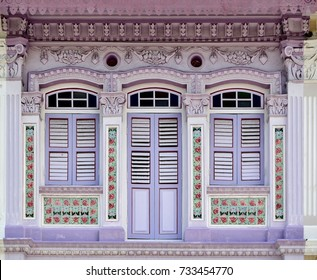 Front view of vintage traditional Peranakan or Straits Chinese Singapore shop house exterior with antique wooden louvered shutters and colorful facade in historic East Coast.