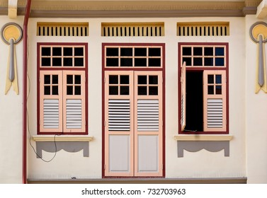 Front view of vintage traditional Straits Chinese or Peranakan Singapore shop house with ornate exterior and antique pink louvered shutters  in historic Chinatown
