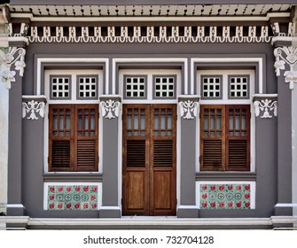 Front view of vintage traditional Straits Chinese or Peranakan Singapore shop house with ornate exterior and antique louvered shutters  in historic East Coast Singapore