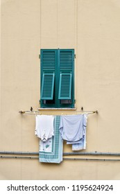 Front view of vintage window with antique louvered shutters on the side wall of a very old building in Italy showing rich tones and textures with space for copy print.