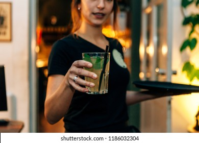 front view of a waitress serving a drink taken from the tray that she holds on the other hand