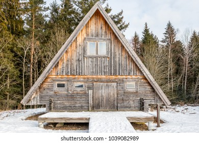 Front view of a weathered and aged log cabin surrounded by trees and snow.