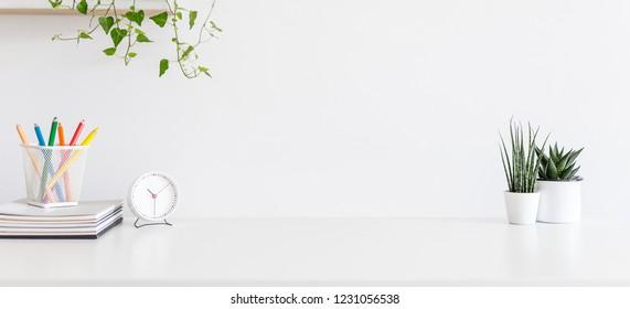 Der weiße Schreibtisch mit Front View mit Vorräten, Wecker, Kaffeemaschine und Kopienraum.