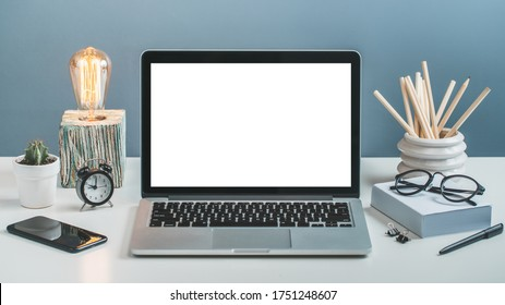 Front view of white office desk with laptop computer with blank white screen and various office supplies. Mock up, copy space for your interface design.