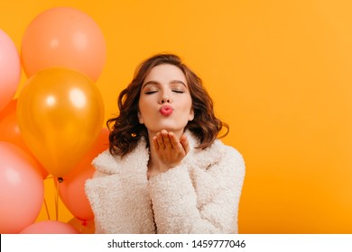 Front view of woman with balloons sending air kiss. Studio shot of birthday girl isolated on yellow background.