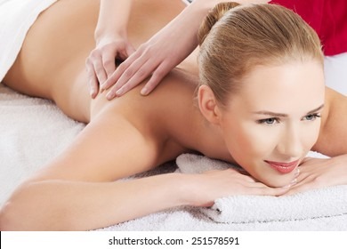 Front view of a woman getting massage in spa.