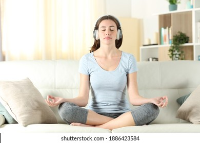 Front view of a woman with headphones listening tutorial meditating doing yoga on a couch at home
