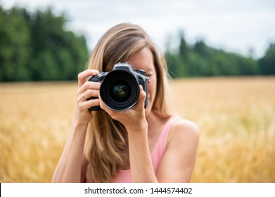 Front view of a woman photographing towards the camera with dslr camera in nature.