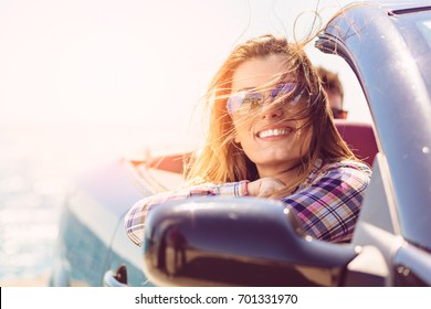 Front view of woman sitting in cabriolet putting hand on door looking away on background of sea.