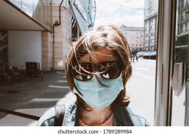 Front view of woman wearing sunglasses and respiratory protective mask in empty city during COVID coronavirus disease pandemic
