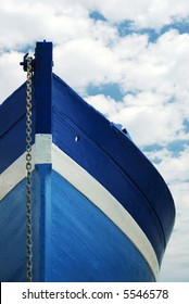Front view of a wooden white and blue row fisherman boat under a cloudy sky