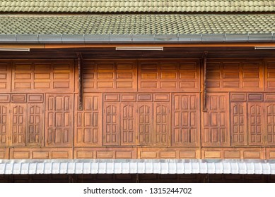 Front view of wooden window with roof tiles, facade of wooden house