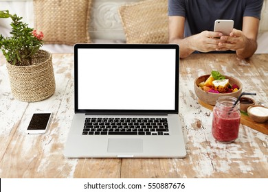 Front view of workplace of self-employed woman or freelancer: generic laptop computer resting on wooden table with smart phone, food and glass of smoothie. Man in background using electronic device