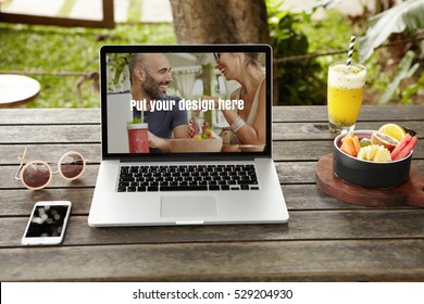 Front view of workspace of female photographer or designer: modern laptop computer with copy space for your design, resting on wooden desk with smart phone, fresh juice, fruits and round shades