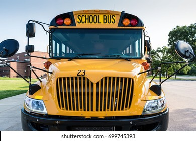 Front view of a yellow school bus parked outside a school - back to school concept