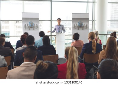 Front view of young Asian businessman speaking in front of diverse group of business people at business seminar in office building