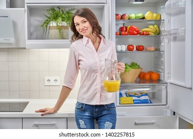 Front view of young attractive woman standing near opened refrigerator, keeping orange juice in hand, looking at camera and smiling. Healthy female drinking fresh juice at kitchen. Concept of health.